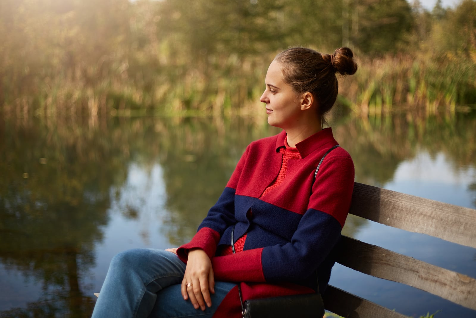 pensive woman sitting on wooden bench on bank of river