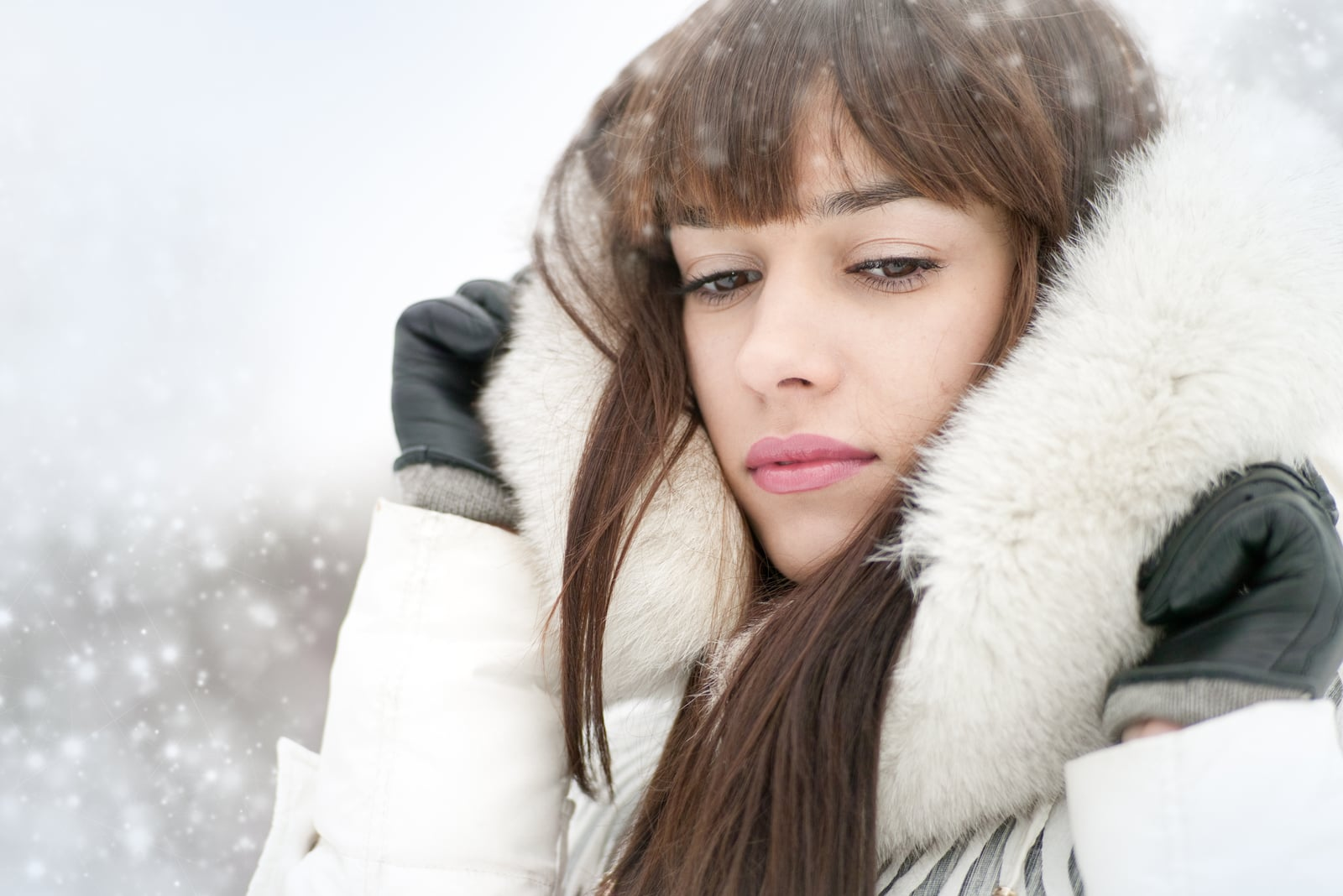 portrait of a sad brunette in the winter on the snow