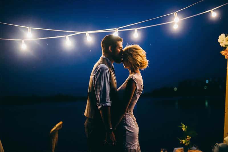 romantic man kisses woman forehead