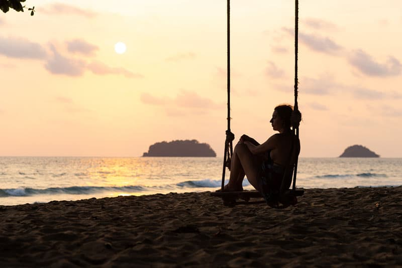 sad woman sitting on swingset