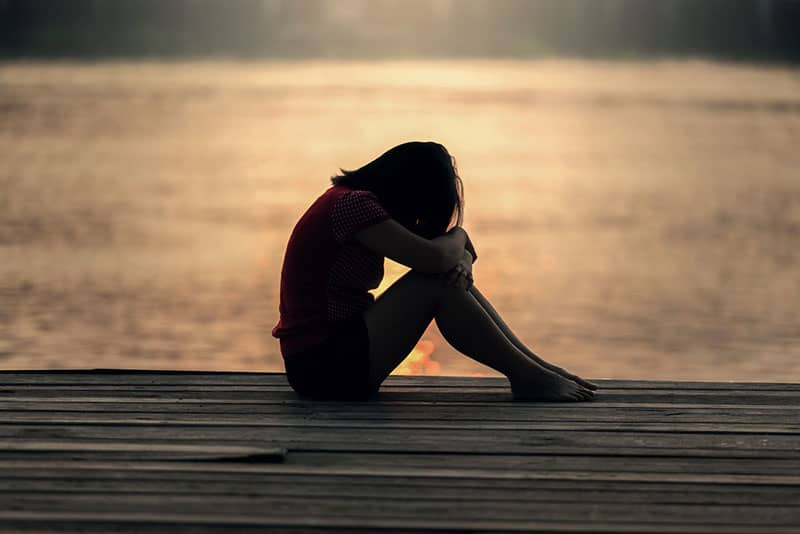 sad young woman sitting by the lake
