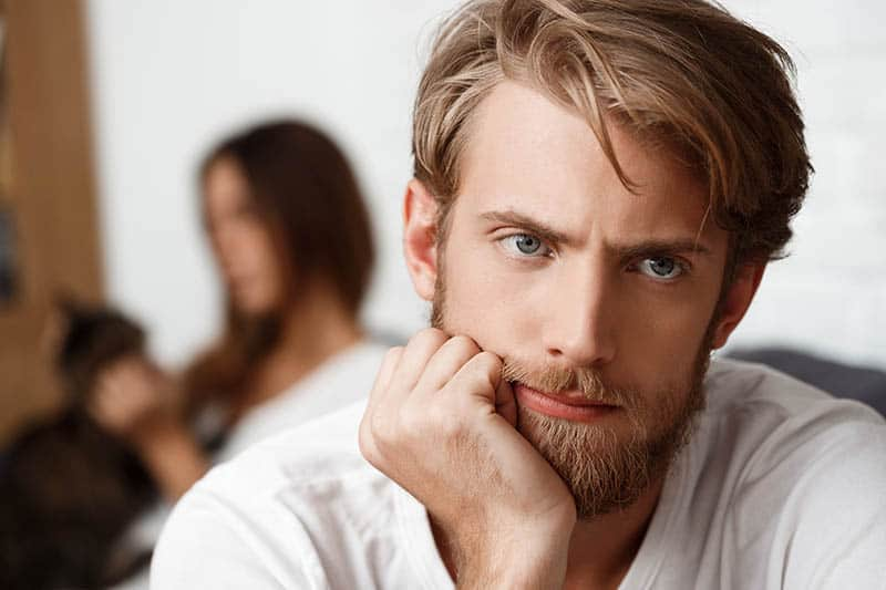 shallow focus of thoughtful man sitting next to woman at home