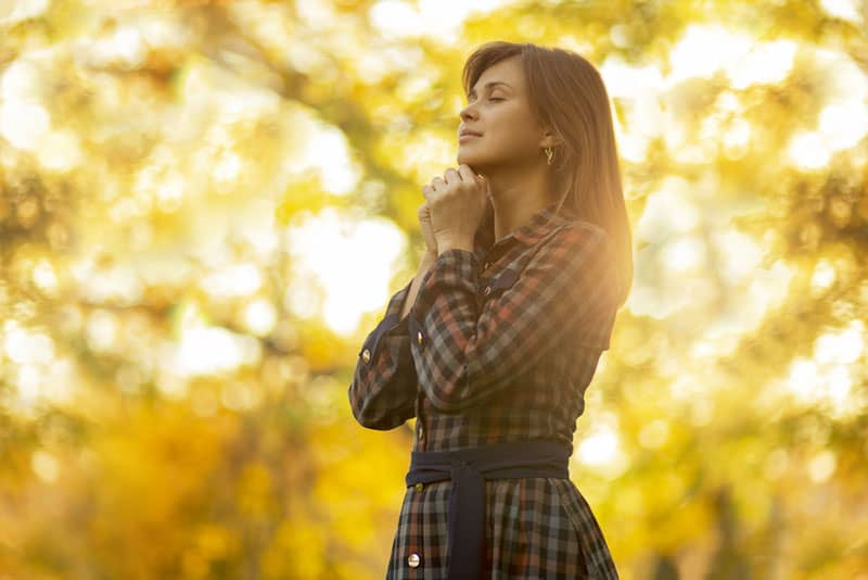 portrait of a young woman praying in nature, the girl thanks God with her hands folded at her chin, a conversation with the Creator, the concept of religion