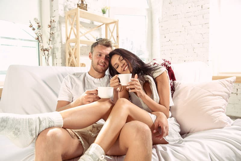 Couple of lovers at home relaxing together. Caucasian man and woman having weekend, looks tender and happy. Concept of relations, family, autumn and winter comfort. Drinking tea and hugging.