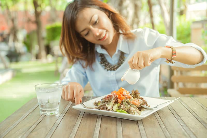 Asian woman and her happiness When eating salad Resting on a plate In the middle of the green garden,Focus on the hand