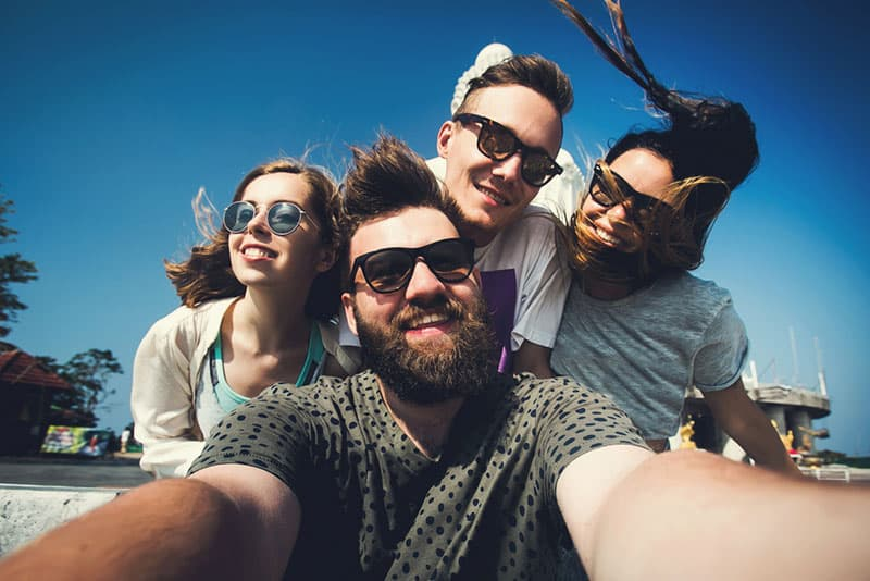 Multiracial group of young hipster friends make selfie photo with smartphone camera in Phuket while traveling across Thailand on vacation. Funny outdoor activity of young students away from home.