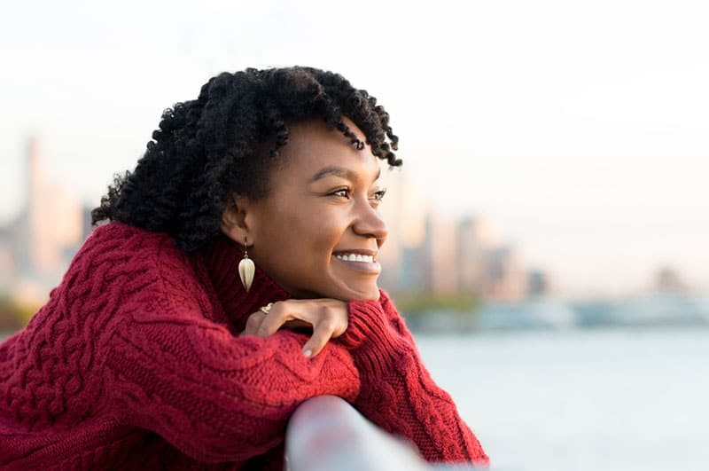 Close up portrait of a young happy african woman leaning on the banister of a bridge near river. Happy young african woman at river side thinking. Smiling pensive girl looking across river at sunset. R