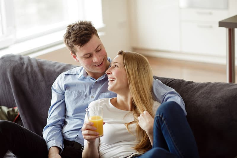 Young couple enjoying themselves on the sofa in the living room. Young man and woman relaxing and drinking the orange juice in the new flat.