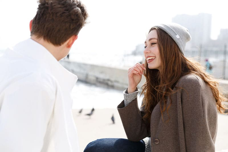 Happy young couple sitting and talking on the beach in autumn