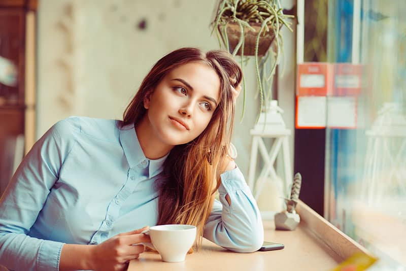 Daydreaming on a coffee break. Pensive happy woman remembering looking at side up sitting in a bar, coffee shop drinking tea