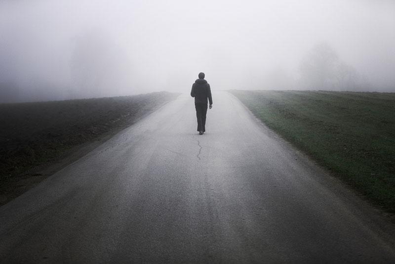 Man alone on foggy road