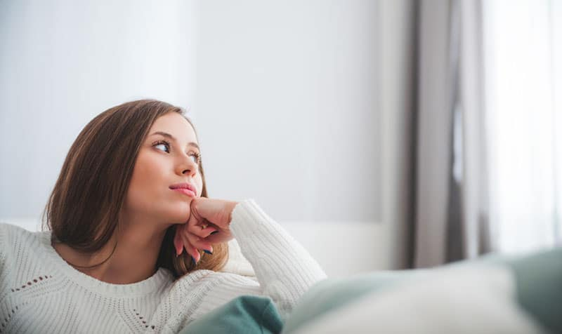 Sad woman sitting on sofa at home deep in thoughts, thinking about important things