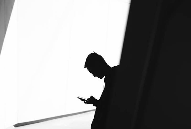 silhouette of man looking on his phone