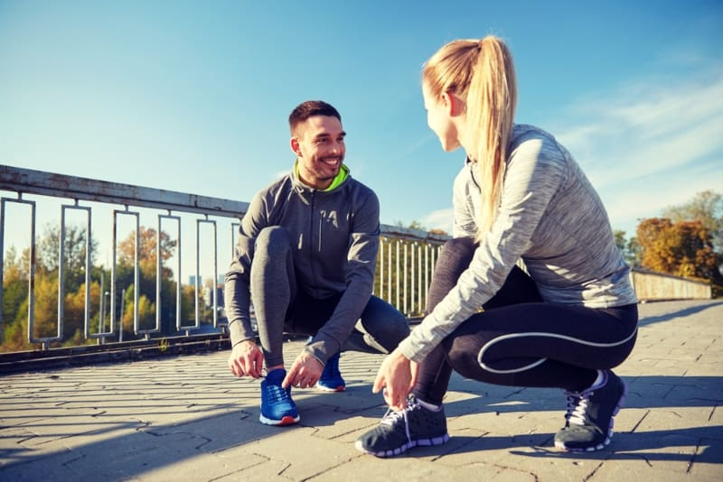 smiling couple tie their shoes on street