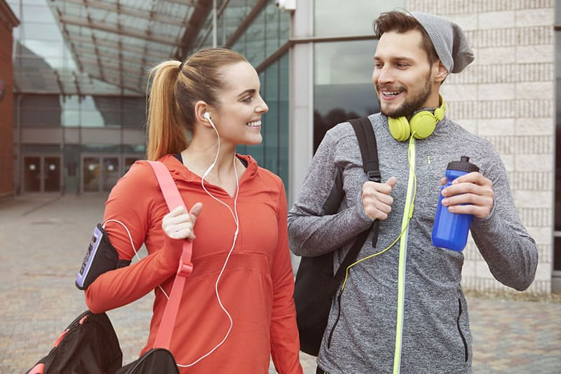 smiling couple walking to the gym