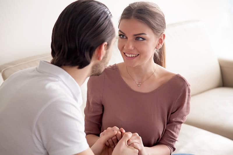 smiling man and woman holding their hands at home