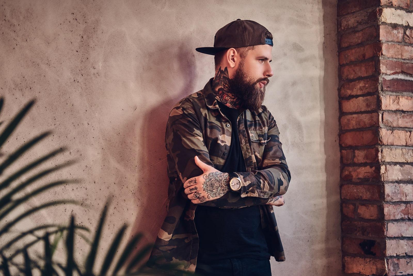 tattooed bearded man standing alone