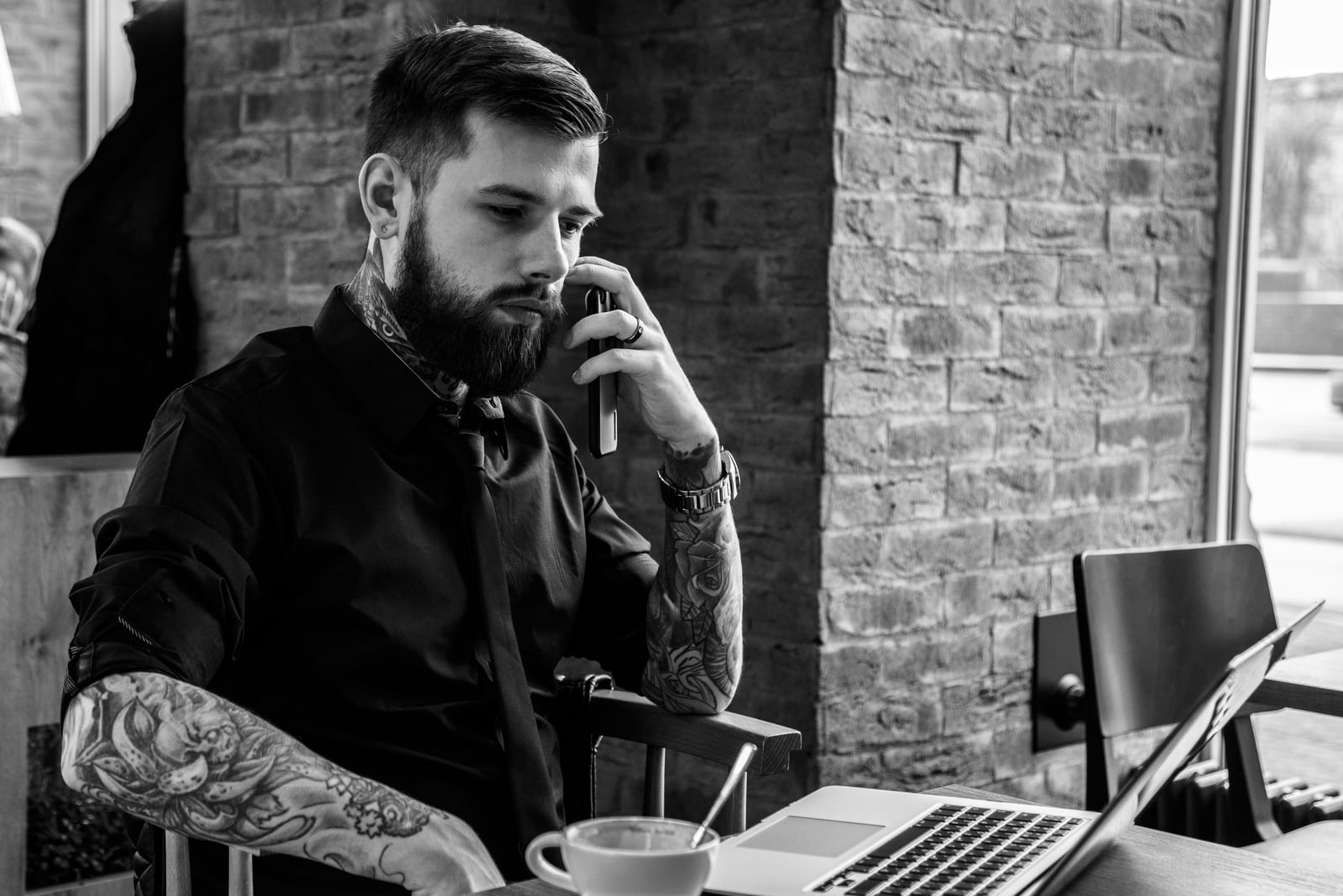 tattooed man sitting by the table