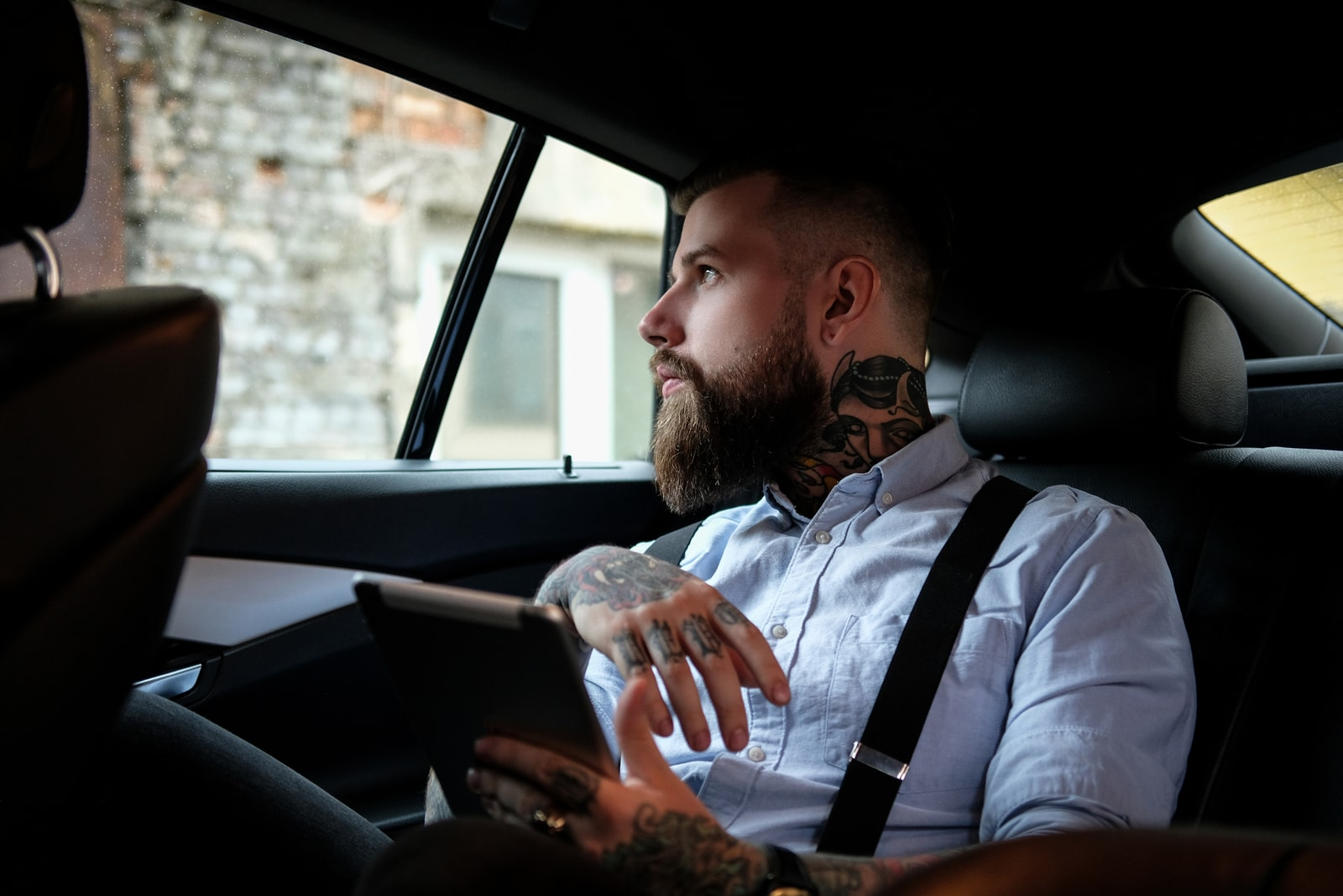 tattooed man sitting in the car