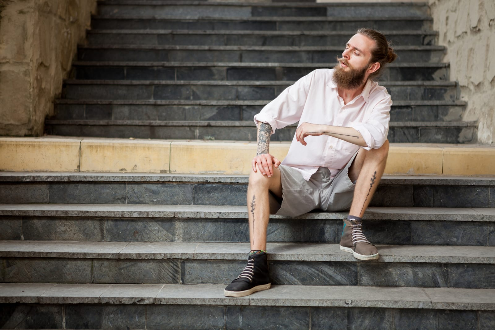 tattooed man sitting on stairs