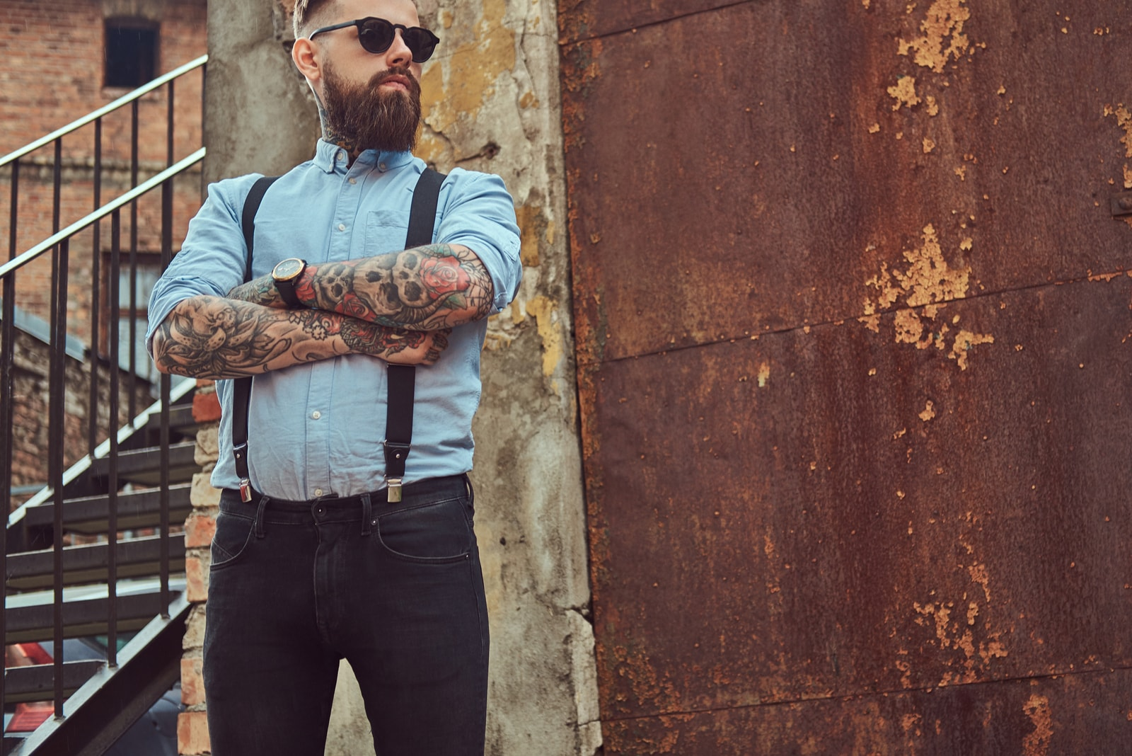 tattooed man wearing watch and sunglasses standing outdoor alone