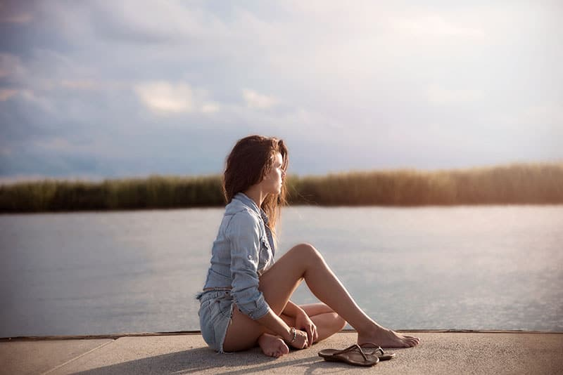 thoughtful woman sitting on dock beside water