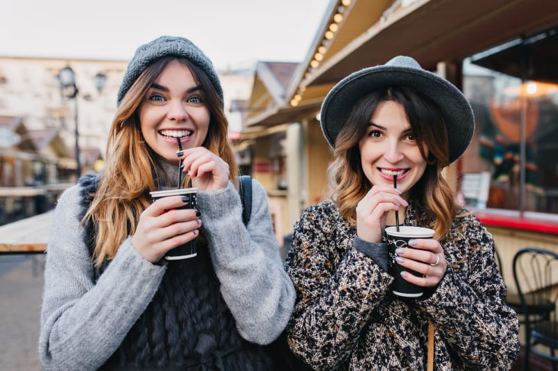 two female friends standing to each other and drinking coffee from cup