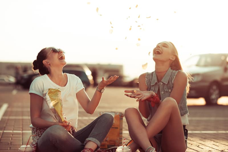 two smiling female friends eating chips outside