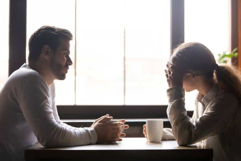 upset couple talking at cafe