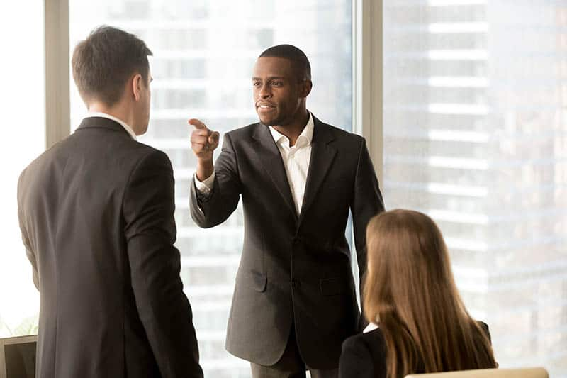 upset man pointing finger at another man in office