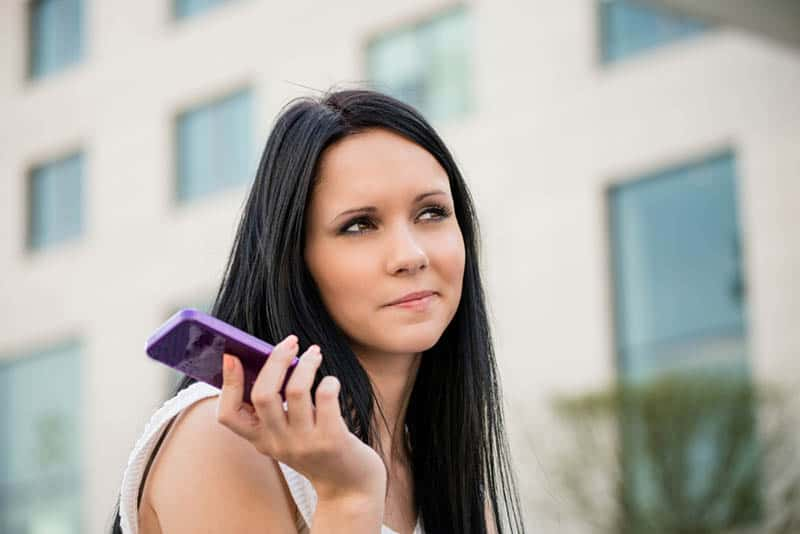 woman holding phone outside