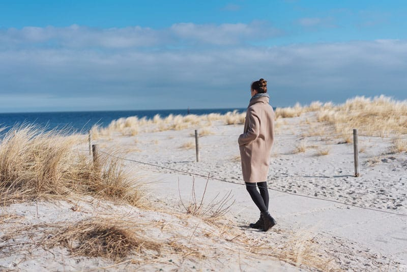woman in coat walking on the beach