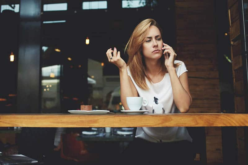 woman looks thoughtful while talking on phone at cafe