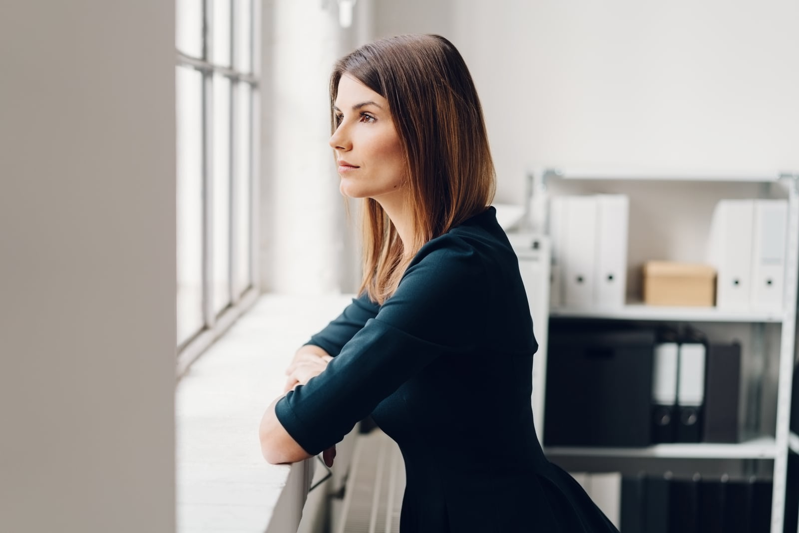 woman standing staring out of a window
