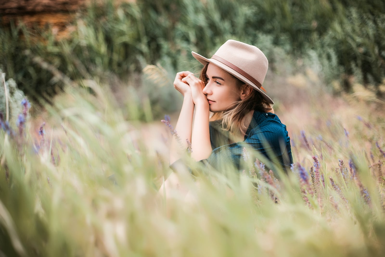 woman wearing hat sitting in a grass on sunny day
