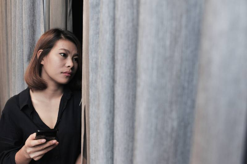 worried woman holding phone and looking outside