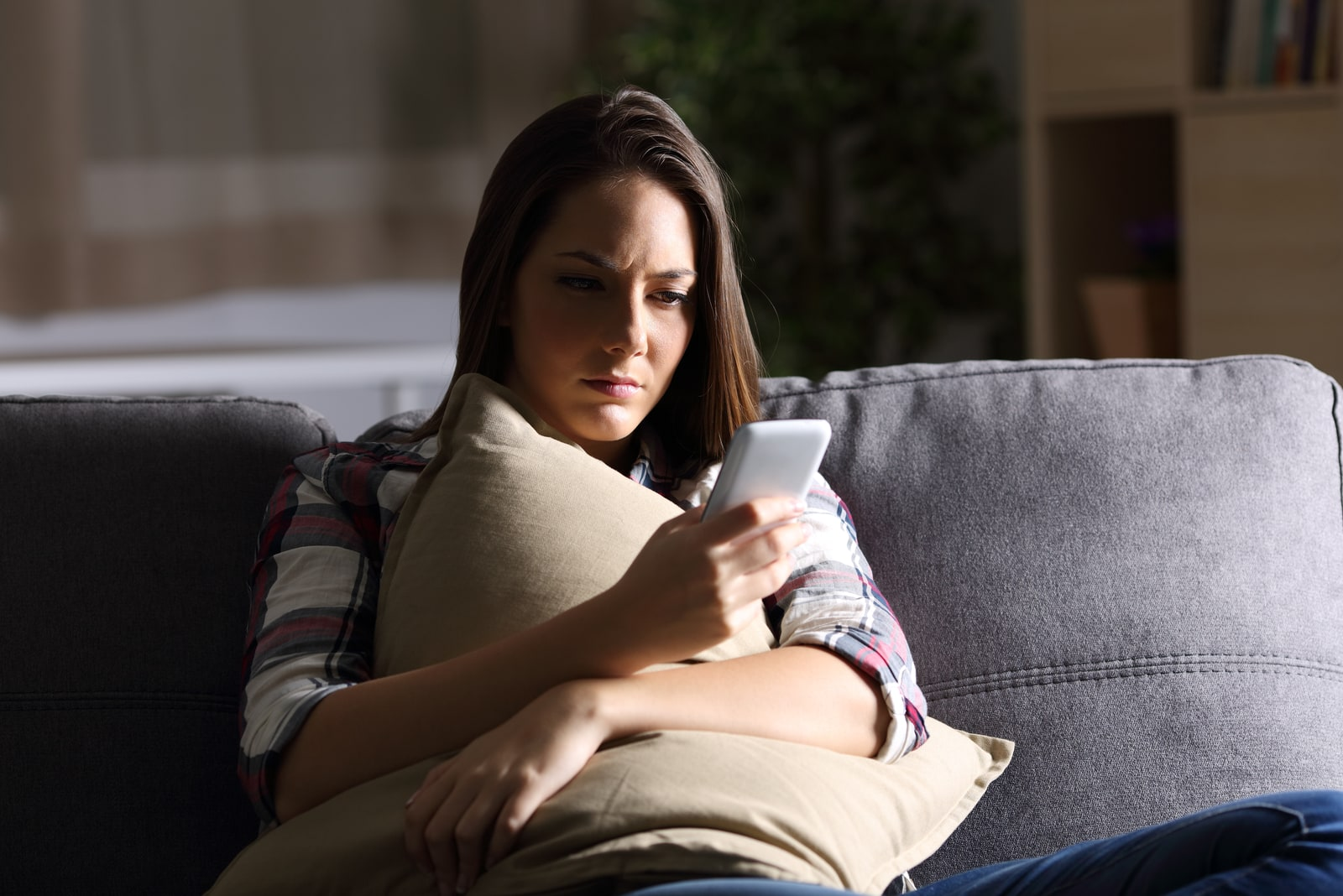 worried woman looking at phone