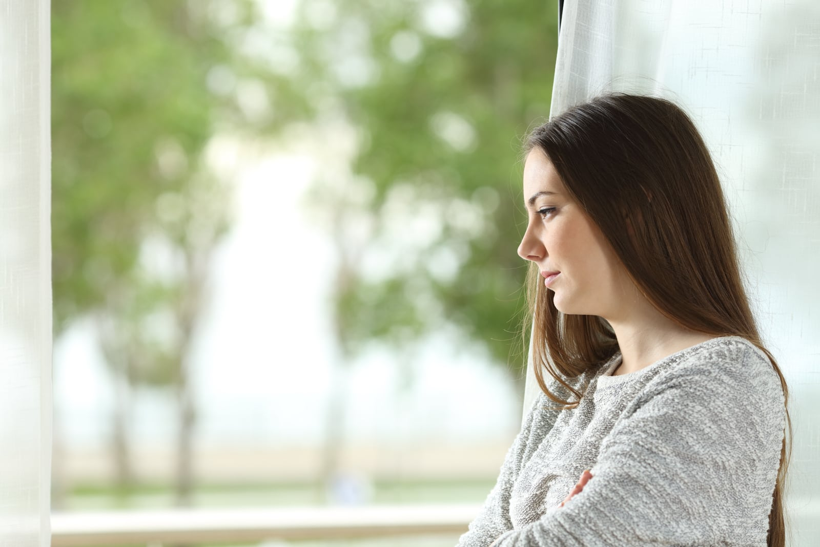 worried young woman standing by the window