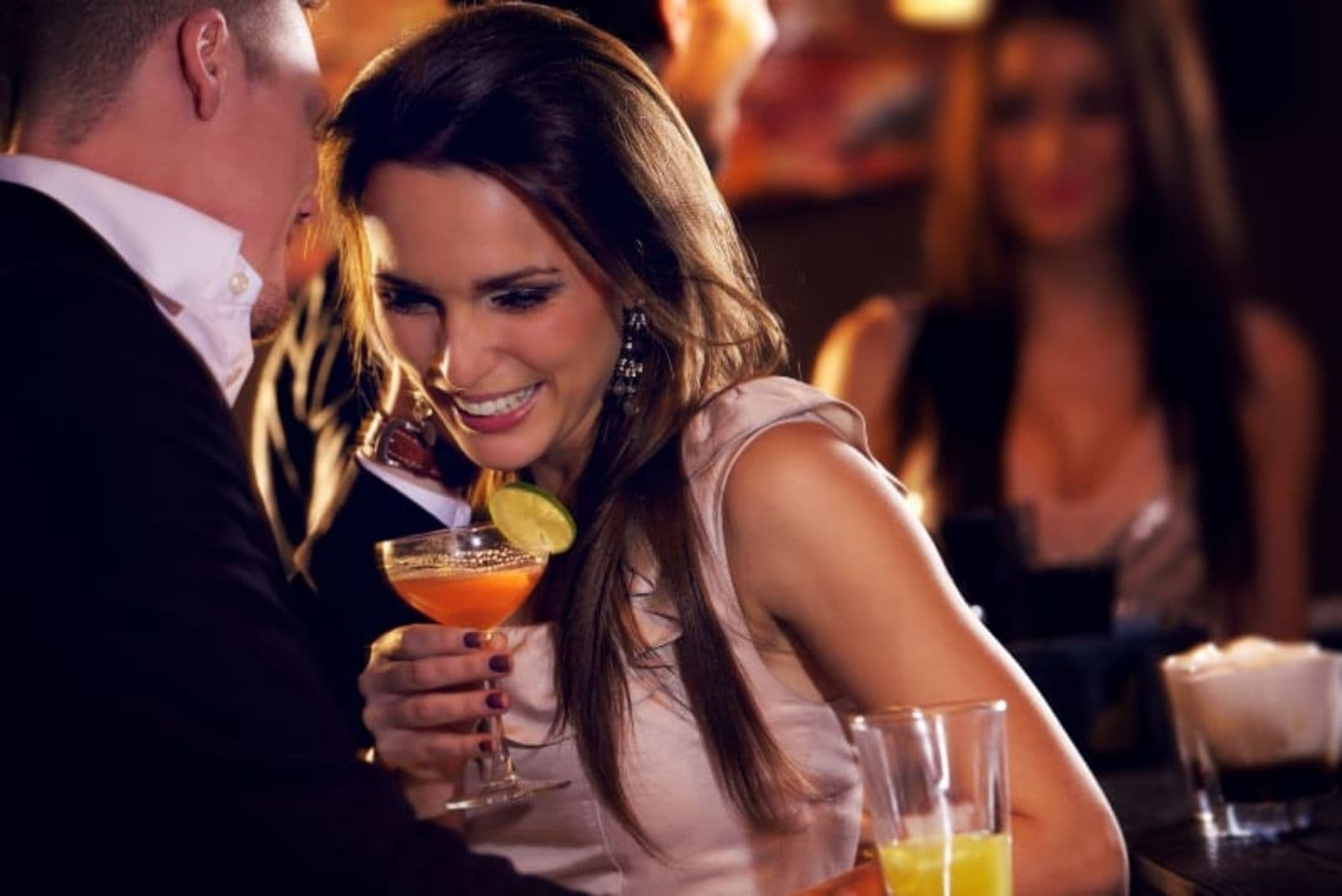 young girl drinking cocktail in night bar and talking with her boyfriend