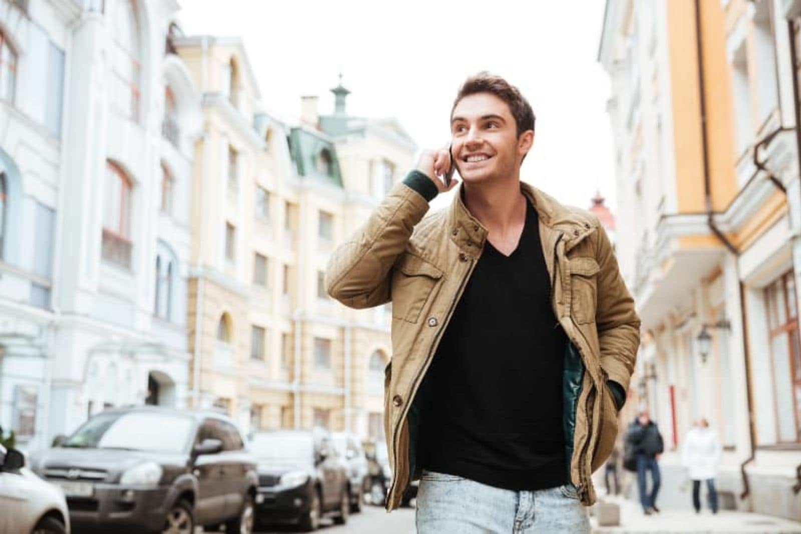 young happy guy walking and talking on his phone