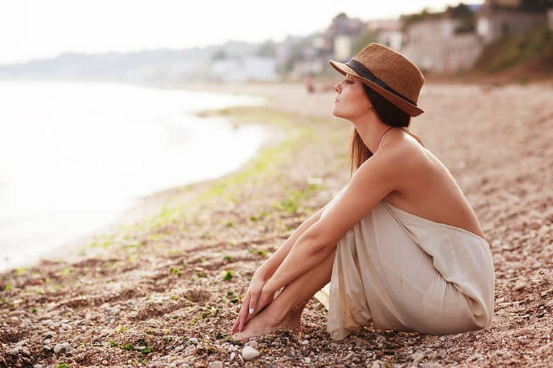 young woman with hat sitting on the beach