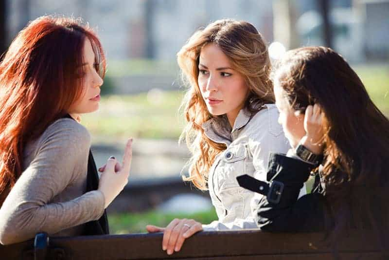 group of girlfriends talking in the park, autumn sunny day