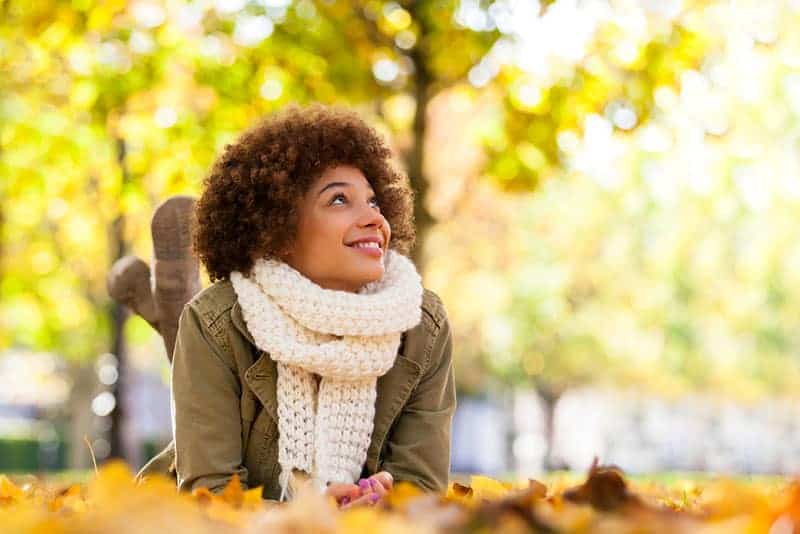 Autumn outdoor portrait of beautiful young woman lying down