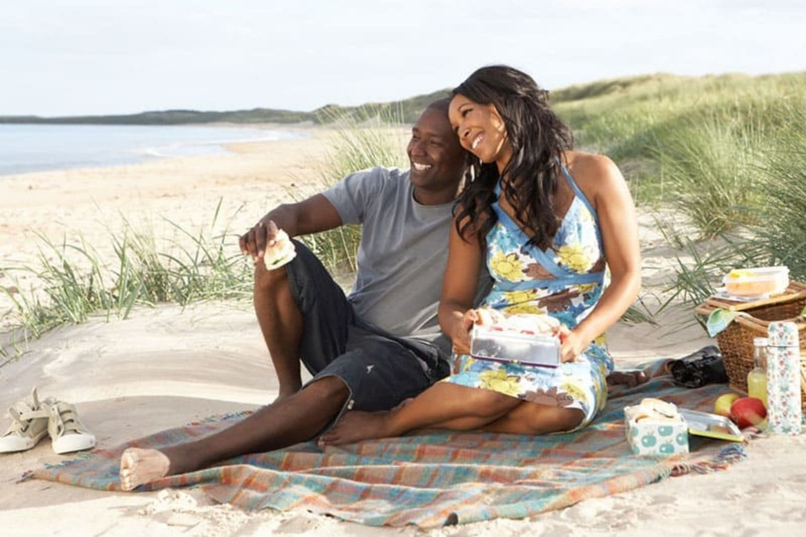 a man and a woman are sitting on the beach