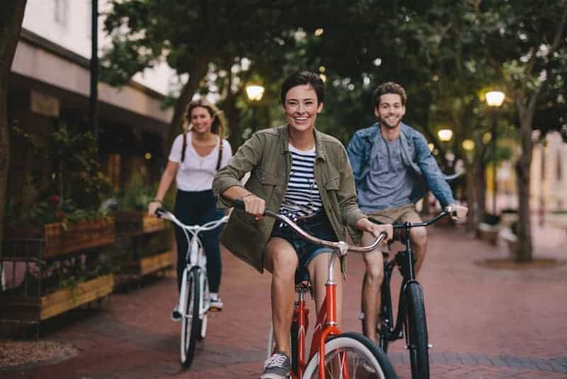 Male and female friends on road with their bikes