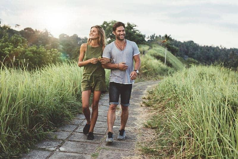 Man and woman walking along tall grass field.