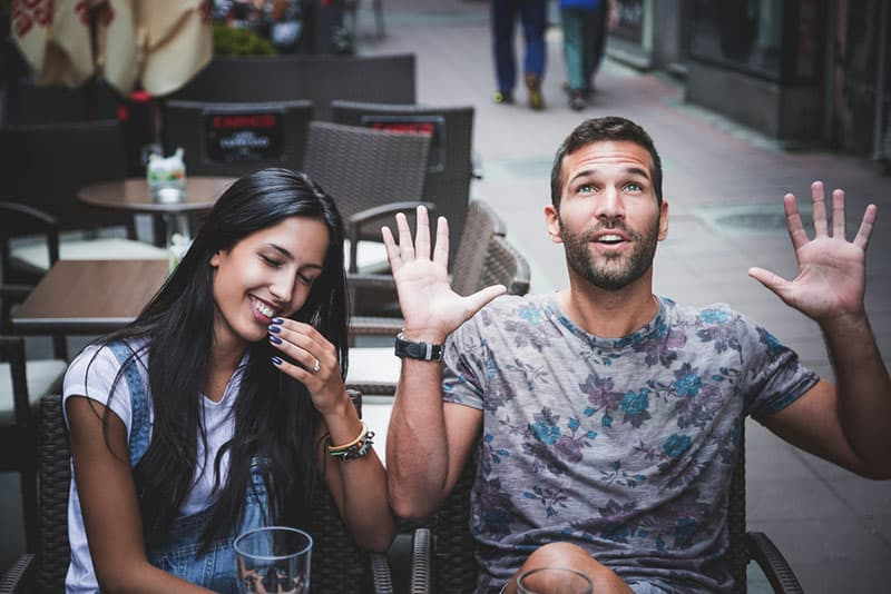 Playful couple laughing in a bar
