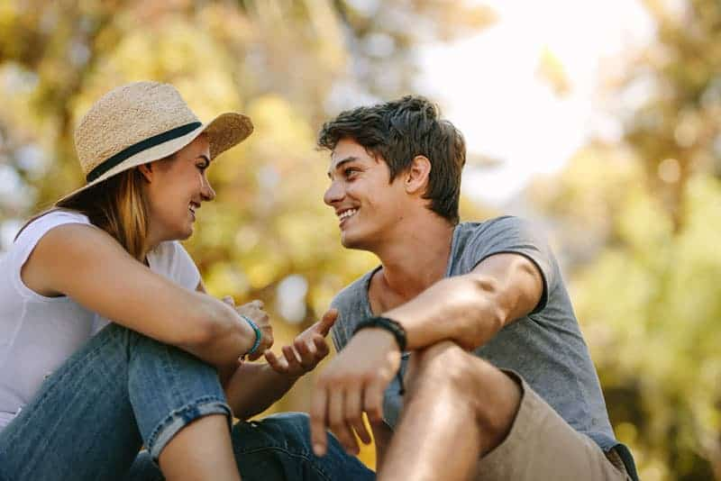 Smiling couple sitting outdoors looking at each other and talking.