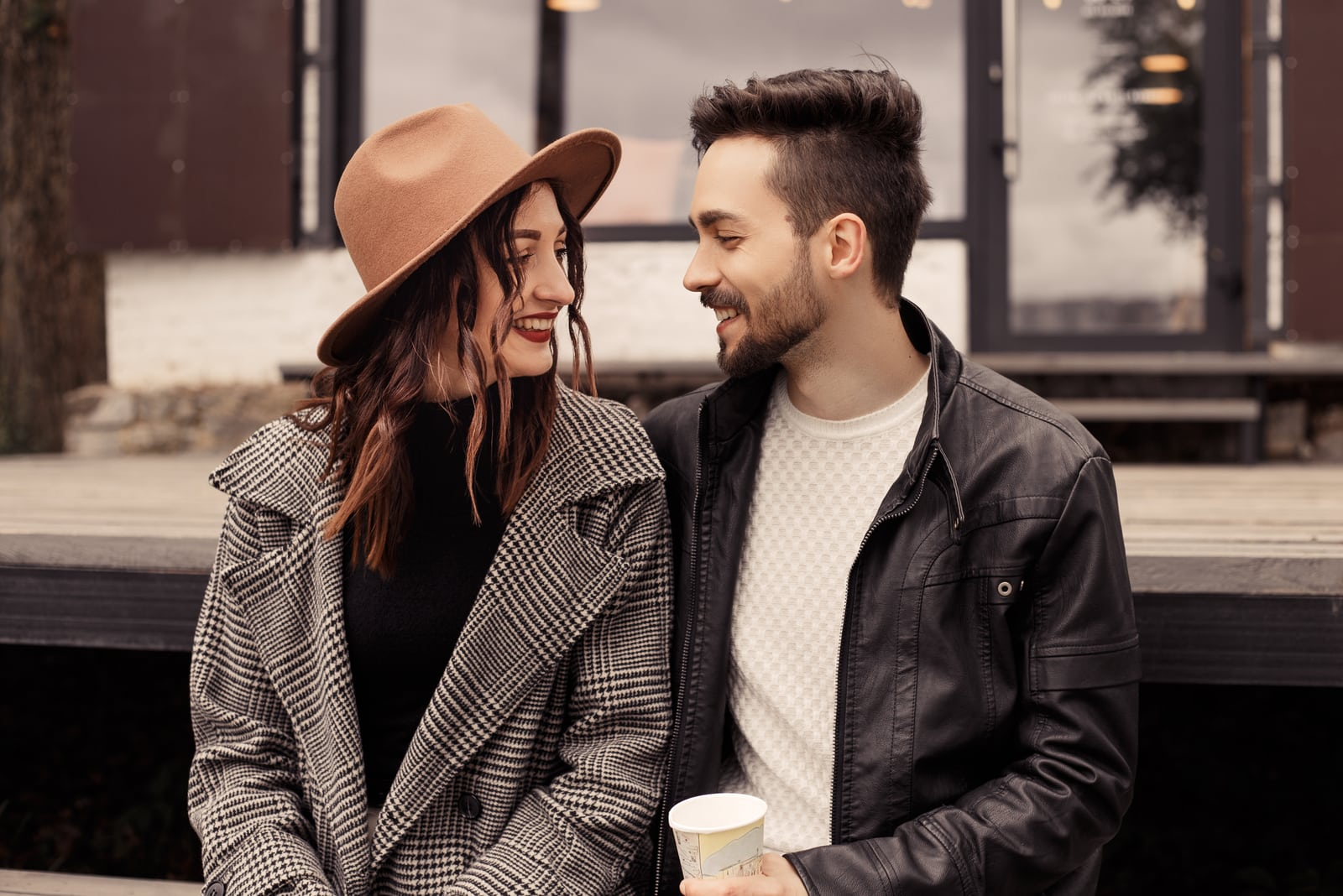 a smiling loving couple sitting outside and talking