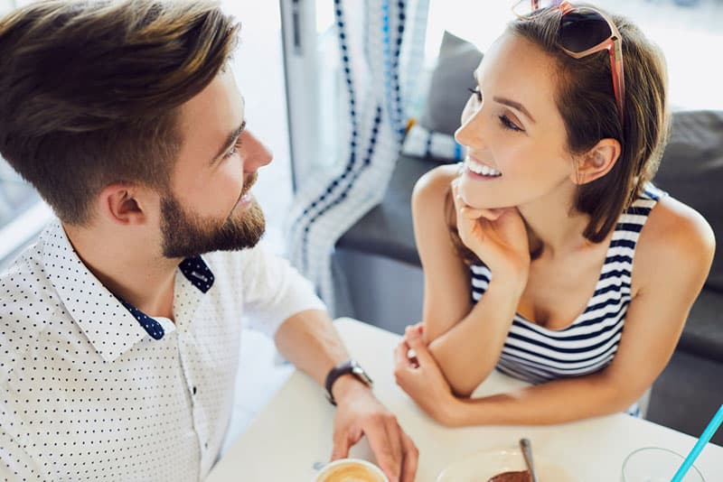 Top view of young couple talking and laughing while sitting in cafeteria relaxing and drinking coffee